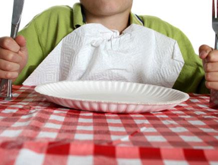 ילד יושב בשולחן עם מפה משובצת מחזיק סכין ומזלג (צילום: huronphoto, Istock)