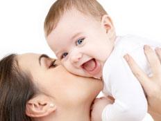 אמא מרימה ומנשקת תינוקת מחייכת (צילום: Lev Dolgachov, Istock)
