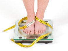 רגליים מלופפות בסרט מדידה עומדות על משקל