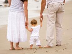 תינוק הולך ומחזיק את ידיהם של הוריו (צילום: digitalskillet, Istock)