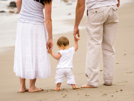 תינוק הולך ומחזיק את ידיהם של הוריו