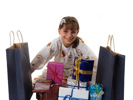 ילדה מחייכת כשמולה מלא מתנות (צילום: getty images)