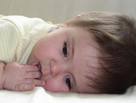 תינוק שוכב כשאצבעותיו בפיו (צילום: Jessica Asmar, Istock)