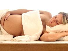 אישה בהריון שוכבת על הצד, מלטפת את ביטנה