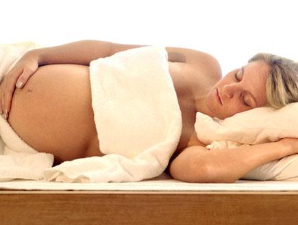אישה בהריון שוכבת על הצד, מלטפת את ביטנה (צילום: jupiter images)