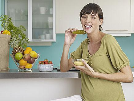 אישה בהריון עומדת במטבח, נינוחה מחייכת ואוכלת (צילום: jupiter images)