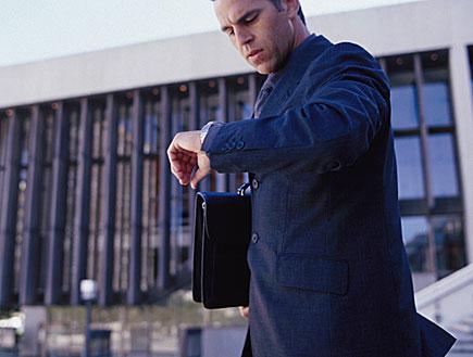 איש עסקים ממהר מסתכל על השעון (צילום: jupiter images)