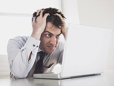 בחור לחוץ מול מחשב נייד (צילום: jupiter images)