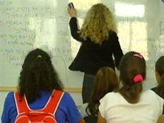 מורה בכיתה כותבת על הלוח, 2 תלמידות מקשיבות