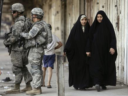חיילים אמריקנים בעיראק, לידם עוברות 2 נשים מקומיות (צילום: אור גץ, רויטרס)