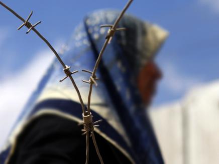 אשה פלסטינית מבעד לגדר תייל (צילום: רויטרס)