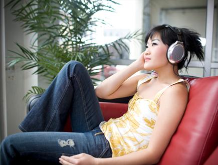 סינית עם אוזניות שומעת מוזיקה (צילום: quavondo, Istock)