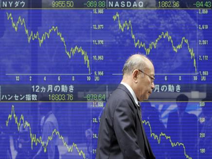 אדם חולף ליד לוח דיגיטלי בורסה בטוקיו (צילום: חדשות)