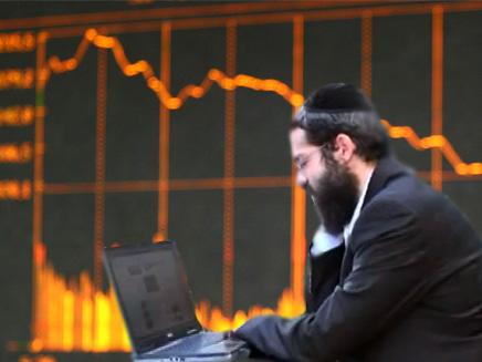 חרדי עם מחשב לרקע נתוני הבורסה (צילום: רויטרס)