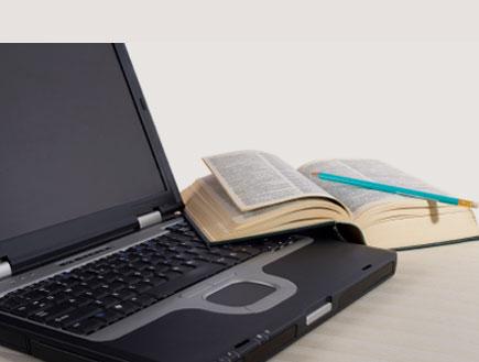 לפטופ וספר פתוח (צילום: marcelmooij, Istock)