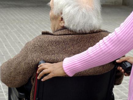מטפלת דוחפת כסא גלגלים (צילום: Carmen MartA-nez BanAs, Istock)