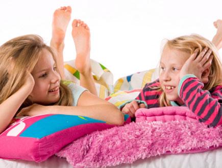 שתי ילדות מדברות במיטה (צילום: DNF-Style, Istock)