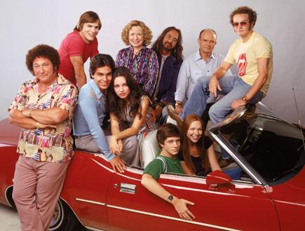כל הקאסט במכונית אדומה עם גג נפתח (צילום: מופע שנות השבעים)