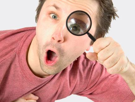 בחור בחולצה ורודה מסתכל דרך זכוכית מגדלת (צילום: rzdeb, Istock)