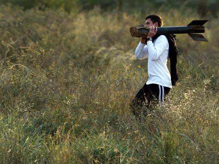 נער ישראלי סוחב שיירי קסאם שנחת בניר עם (רויטרס) (צילום: רויטרס)