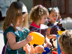 ילדות בגן משחקות בבובות