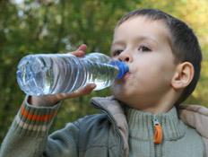 ילד שותה מים מינרליים מבקבוק