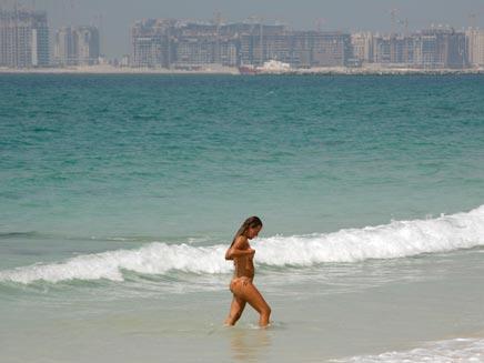תיירת על חוף בדובאי (צילום: רויטרס)