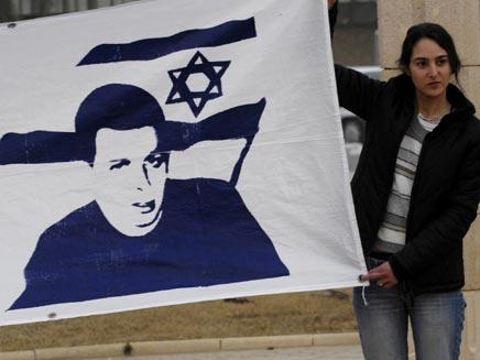נערה מחזיקה דגל של גלעד שליט (רויטרס) (צילום: חדשות 2)