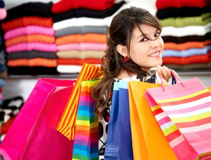 בחורה בחנות בגדים מחזיקה שקיות קניות (צילום: Vostock Photo, Istock)