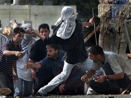 פלסטינים משליכים בקבוק תבערה. ארכיון (צילום: רויטרס)