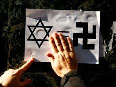 כרזה המשווה בין המגן דוד לבין צלב הקרס (רויטרס) (צילום: רויטרס)