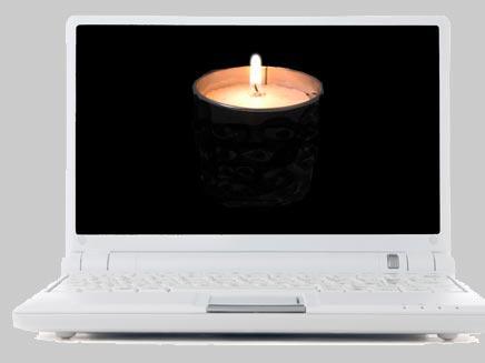 מחשב נייד עם נר זיכרון במסך (צילום: Dmitrii Kshanovskii, Shutterstock)