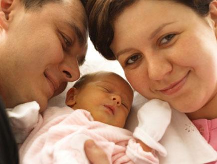 הורים מחזיקים תינוקת קטנה (צילום: damircudic, Istock)