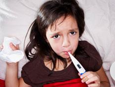 ילדה מודדת חום במיטה