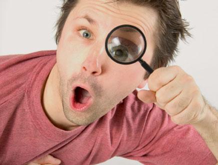 איש משתמש בזכוכית מגדלת (צילום: rzdeb, Istock)