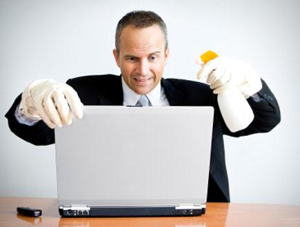 גבר מנקה מחשב (צילום: swilmor, Istock)