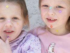ילדות מדביקות מדבקות על הפנים