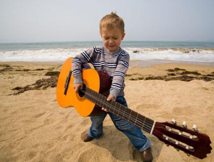 ילד מנגן בגיטרה בים (צילום: stask, Istock)
