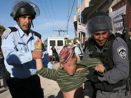 שוטרים אוחזים בכוח ילד מתנחל בחברון (צילום: רויטרס)