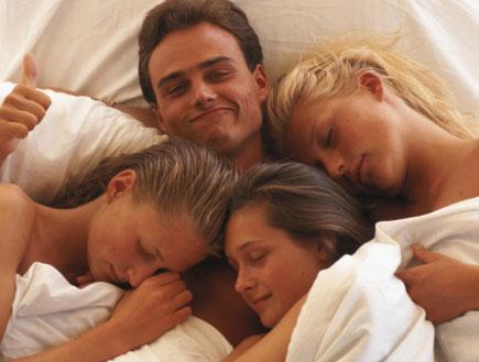 בחור ושלוש בנות במיטה
