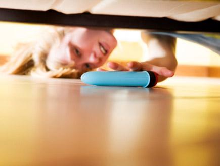 אשה מחביאה ויברטור מתחת למיטה (צילום: diego_cervo, Istock)