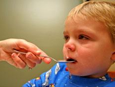 ילד חולה עם כפית בפה (צילום: DIGIcal, Istock)