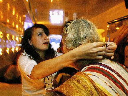 הילרית מניחה את ידיה על ראשה של מטופלת (צילום: Chris Jackson, GettyImages IL)