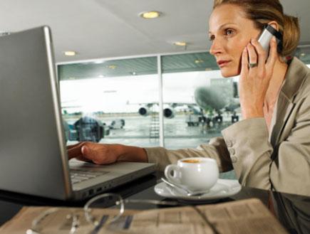 אשה עם מחשב ופלאפון בשדה תעופה (צילום: John Rowley, GettyImages IL)