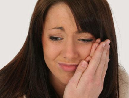 אישה מחזיקה את הפה סובלת מכאב שיניים (צילום: Jaimie Duplass, Istock)