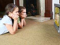 ילדים שוכבים על השטיח וצופים בטלויזיה (צילום: dorioconnell, Istock)