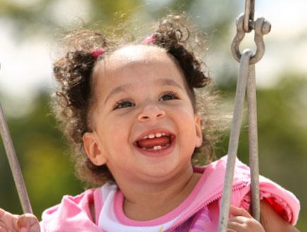 ילדה מחייכת על נדנדה (צילום: Studio1One, Istock)