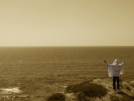 """דתי וגאה - גבר עטוף בתלית עם צבעי הגאווה נושא ידיו (צילום: דרור - עורך אתר הו""""ד)"""