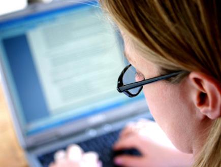 מסתכלת על מסך מחשב ומקלידה (צילום: spxChrome, Istock)