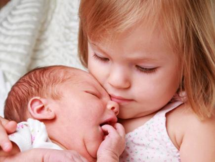 ילדה מחזיקה תינוק- שינויים במשפחה (צילום: RoyalFive, Istock)